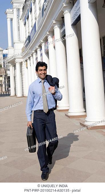 Businessman walking with a briefcase, Gurgaon, Haryana, India