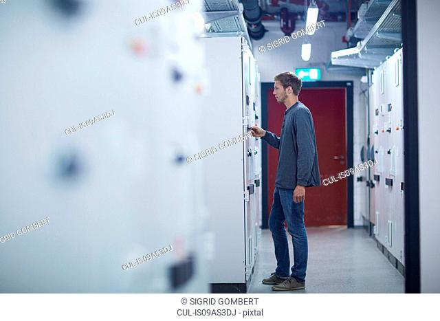 Male technician turning switch on in technical room