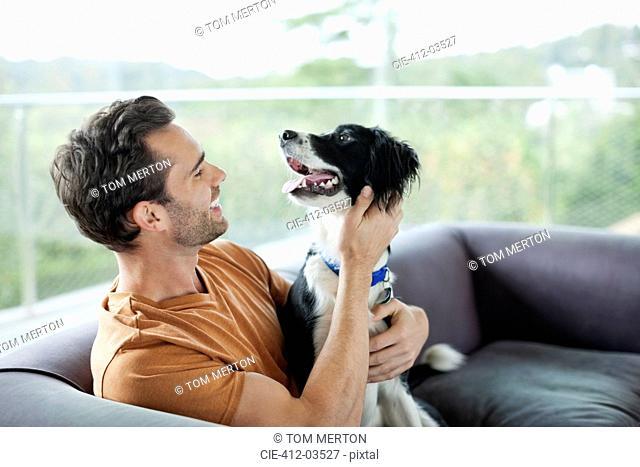 Smiling man petting dog on sofa