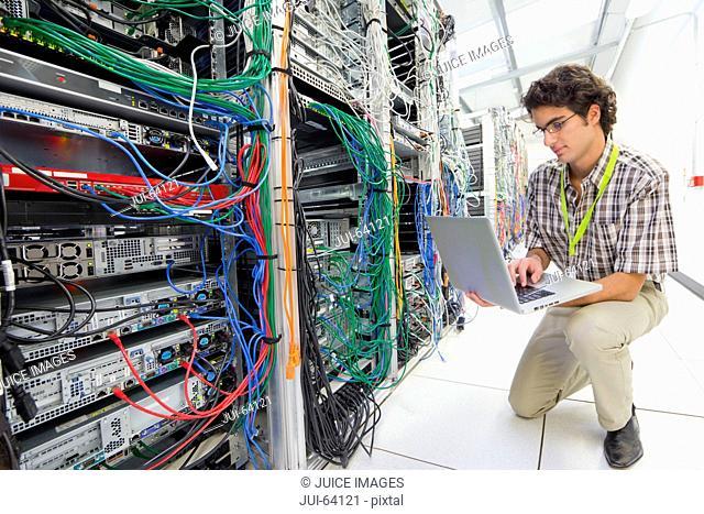 Technician, kneeling, working on laptop computer in Server room of data center