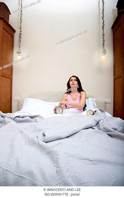 Woman in bed holding alarm clock
