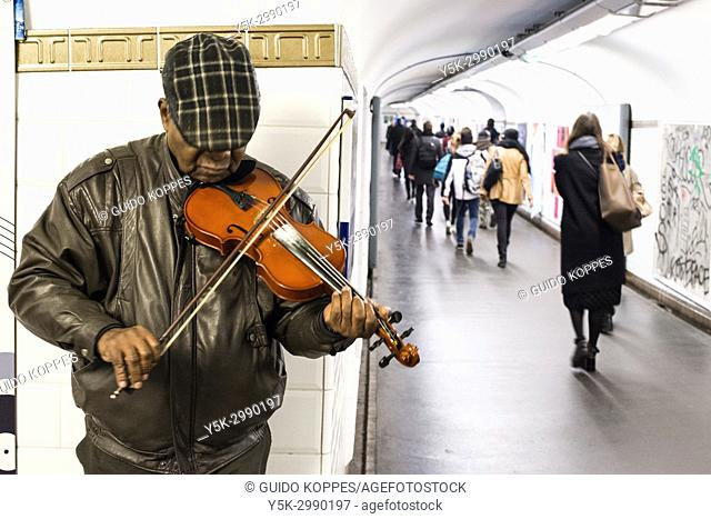 Paris, France. Mature adult male musician performing his music inside Chatalet Subway Station. Music in the French Underground system is wide spread