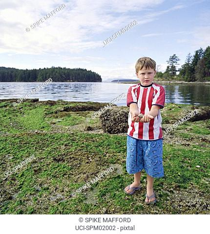Young boy holding rock by river