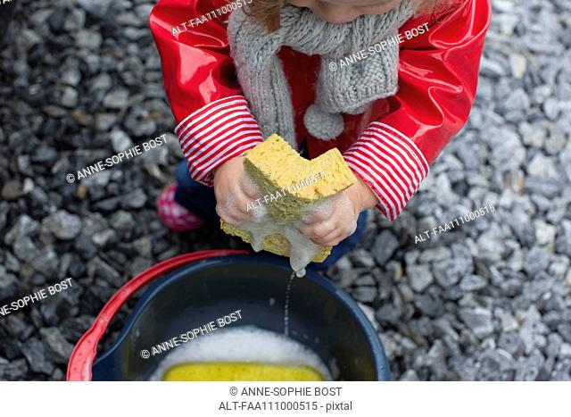 Child holding soapy sponge