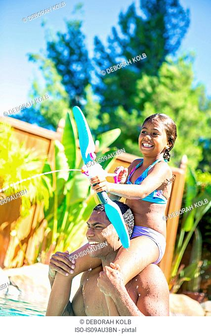 Daughter sitting on fathers shoulders playing with water pistol smiling