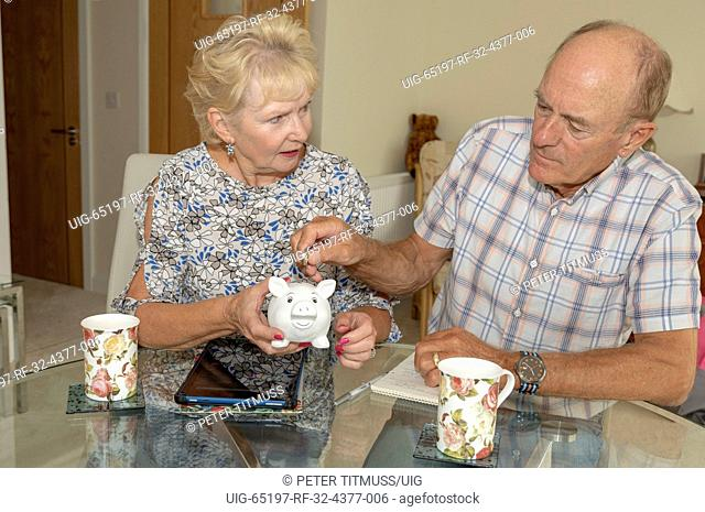 Mature couple checking their expenditure and savings, Man placing money into piggy bank
