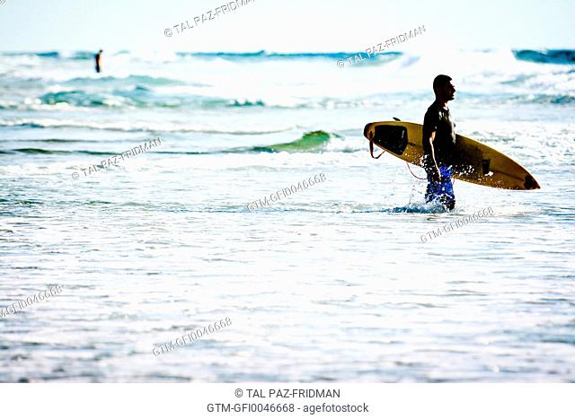 Surfer walking towards the waves