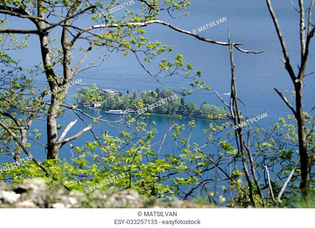 Island on a lake with trees and passenger ship