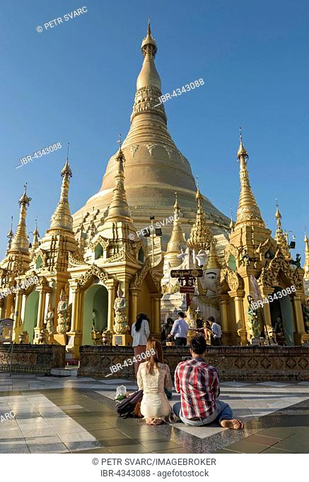Young couple praying at Shwedagon Pagoda, Yangon, Rangoon, Myanmar