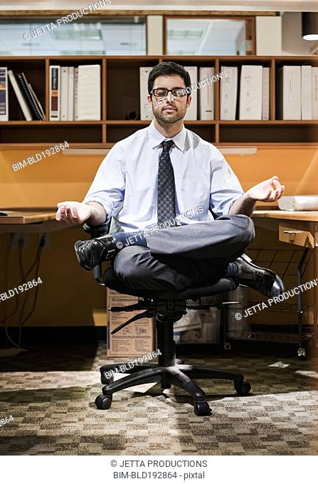 Hispanic businessman meditating at desk