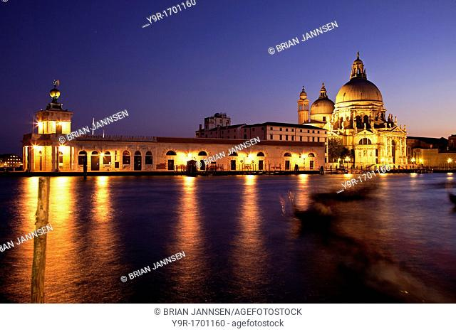Grand Canal at dusk with Santa Maria della Salute and shadowy gondolas drifting by in Venice Veneto Italy