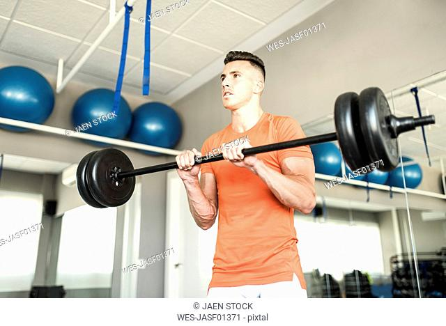 Man training triceps with bar