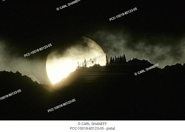 Enormous sunball sinking behind mountaintop, black clouds