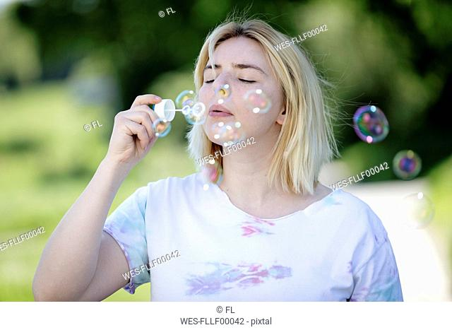 Young blonde woman blowing soap bubbles outdoors