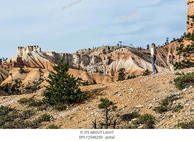 A woman stands viewing the rock formations in Bryce Canyon National Park; Utah, United States of America