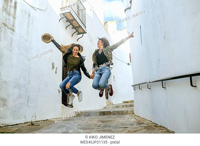 Two happy young women jumping in an alley of a town