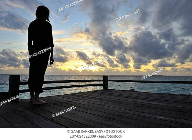 Silhouette of a woman contemplating the sunrise, Island of Borneo, Sabah State, Malaysia