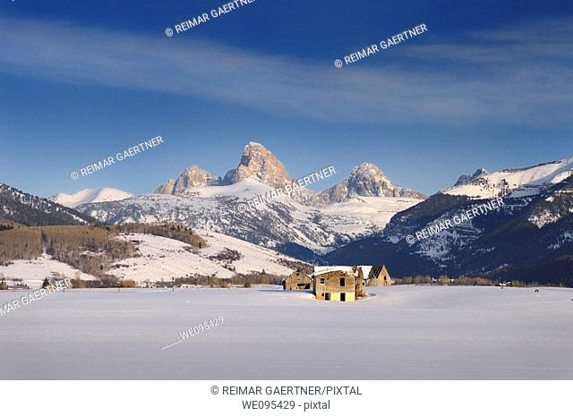 Old abandoned farm buildings in winter evening in Idaho with Grand Teton peaks Wyoming