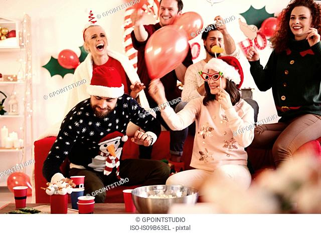 Young women and men having fun laughing at christmas party