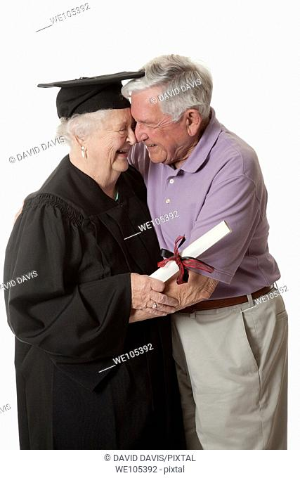 Beauitiful Caucasian woman in a black graduation gown with her husband
