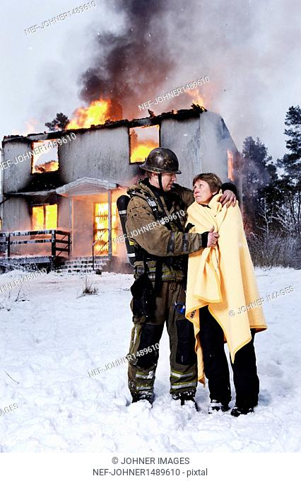 Fireman with rescued senior woman in front of burning house