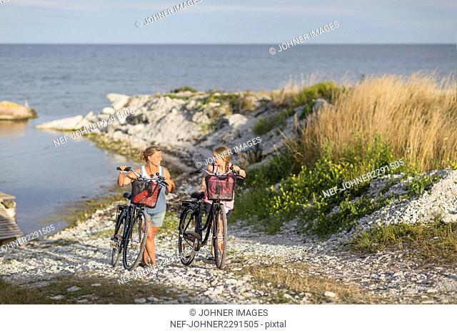 Young women cycling on sea coast