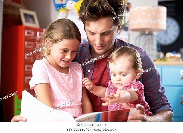 Father Reading Book With Daughters In Bedroom