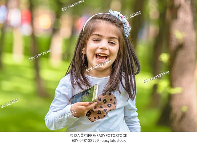 Adorable four years old cute little girl in casual clothes holds mobile phone while laughing at outdoor in park