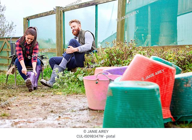 Young couple on farmland putting on rubber boots