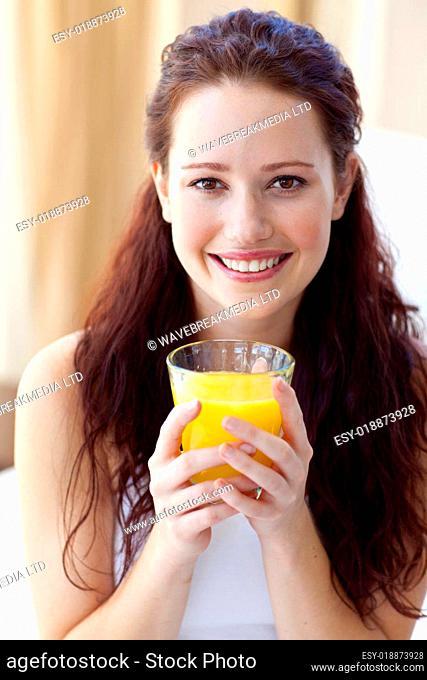 Smiling woman drinking orange juice in bedroom