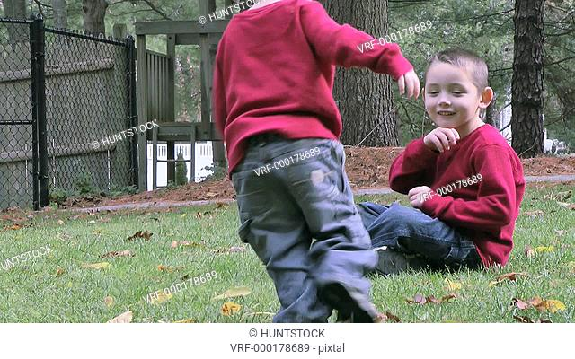Two brother playing at front yard and using American Sign Language saying: Sit down