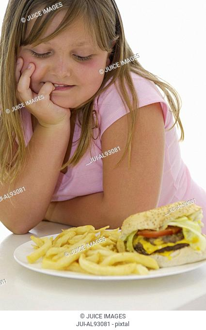 Overweight girl looking at hamburger and french fries
