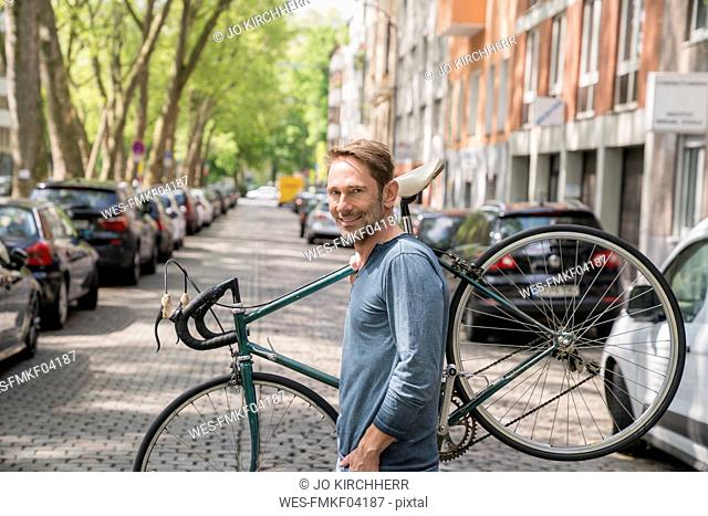 Portrait of smiling mature man carrying his bicycle on the shoulder