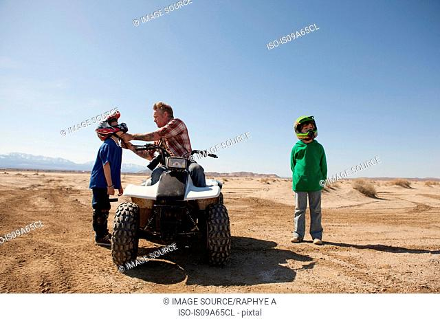Father and sons on four-wheeler