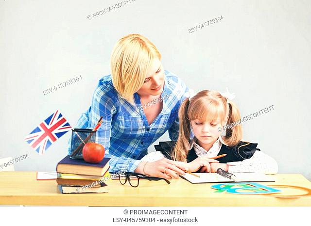 Pretty adult female teacher helps kid girl to learn English language, school table with books, flag and letters in light classroom