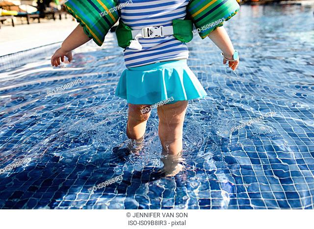 Young girl walking in shallow water in outdoor swimming pool, rear view, low section