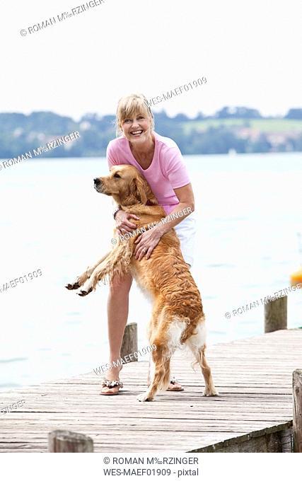 Germany, Bavaria, Starnberger See, Senior woman with Golden Retriever on jetty