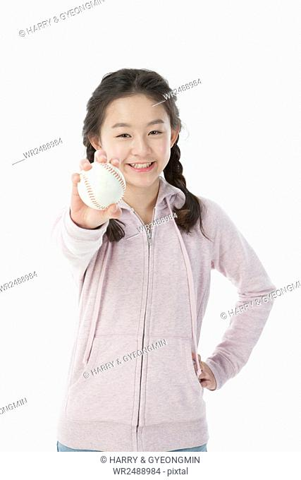 Portrait of smiling school girl posing showing a baseball