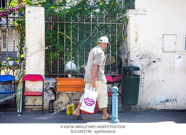Caucasian older senior retired woman walking the streets of fort de france in Martinique in front of an iron gate. She has a straw hat and shopping bags