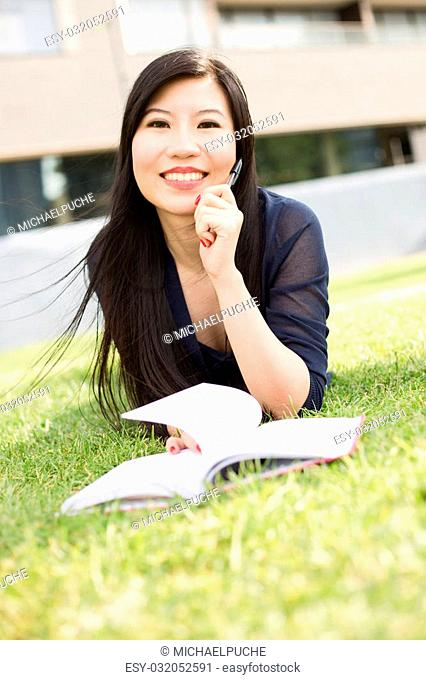 Young japanese woman lying on the grass with a book and pen