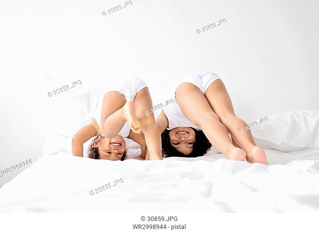 Two girls with curly black hair lying on a bed, smiling, trying to do handstand
