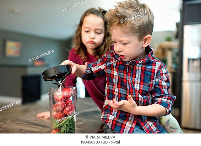 Little girl watching brother cover blender filled with beets and vegetable