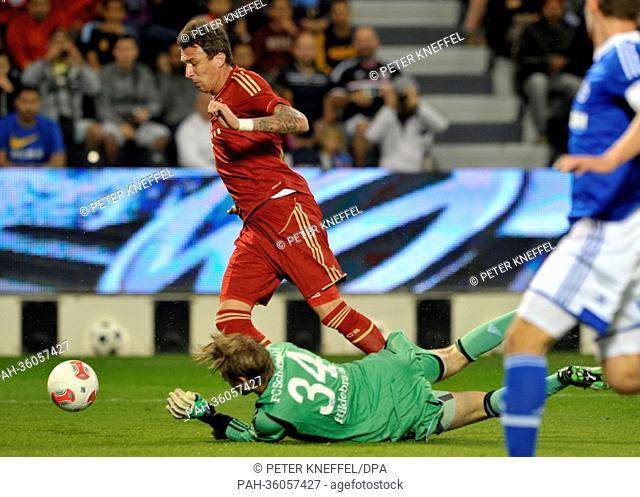 Schalke's goalkeeper Timo Hildebrand (below) vies for the ball with Munich's Mario Mandzukic during a test match between FC Schalke 04 and FC Bayern Munich at...