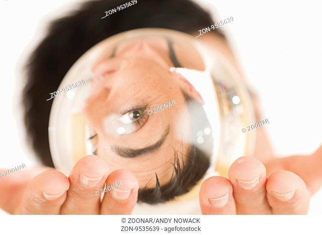 Frontale Kopf-Ansicht einer schwarzhaarigen Frau mittleren Alters blickt durch eine vor das Gesicht gehaltene Glaskugel in die Kamera vor weißen Hintergrund