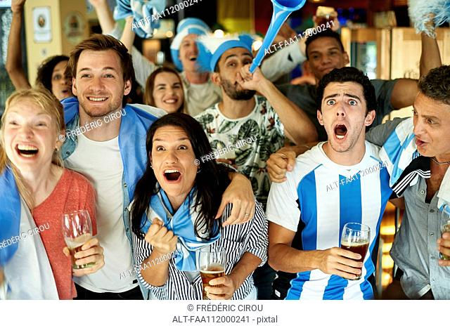 Argentinian soccer fans watching match together at pub