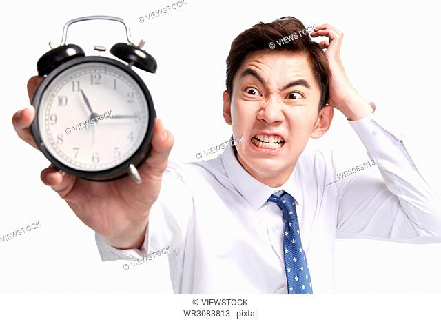 Expression of pain business young man with an alarm clock