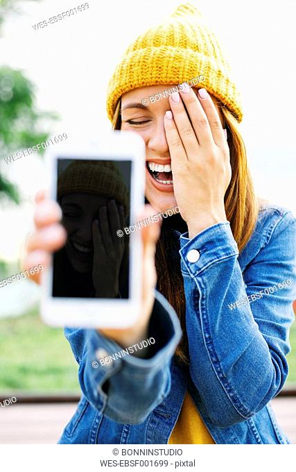 Portrait of laughing young woman showing smartphone with her own picture