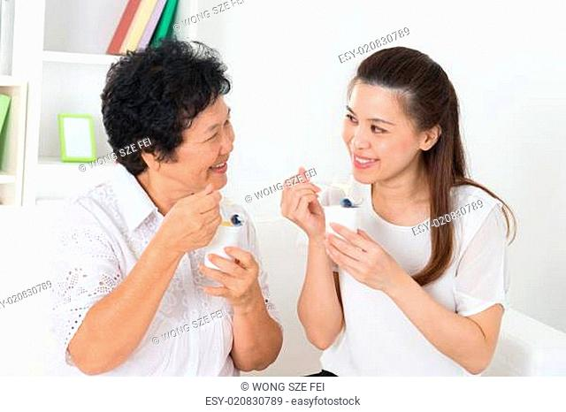 Asian women eating yogurt