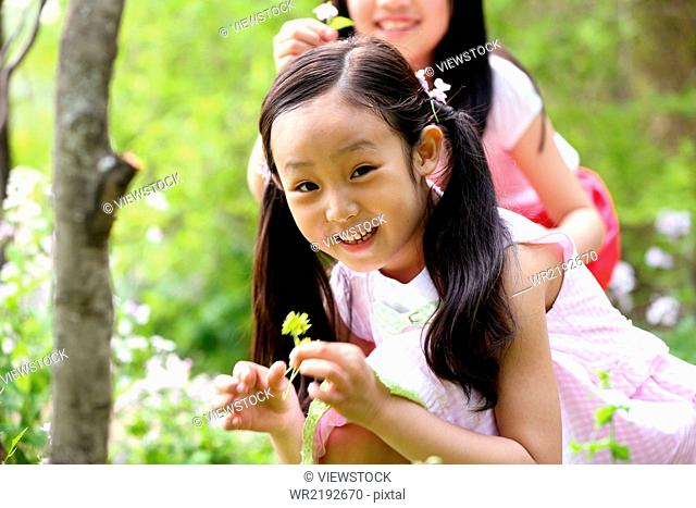 Two girls picking flower in field