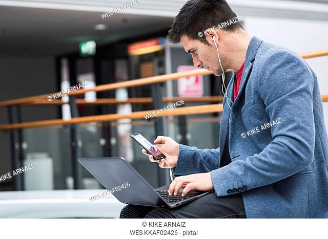 Businessman in lobby of a modern building, using smartphone and laptop